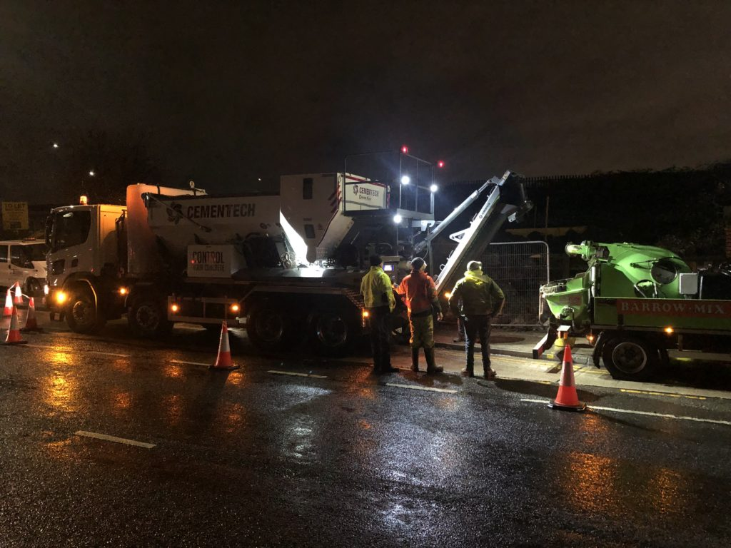 Operators pouring concrete with a C60 volumetric mixer during the night.